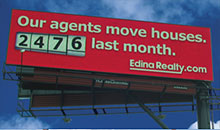 A real estate billboard showing how many homes agents sold last month