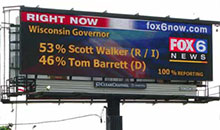 A digital billboard displaying live political campaign results