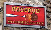 A 'Rosebud: welcome to Big Italy' message featuring a big meatball on a fork, is displayed on a junior poster billboard.