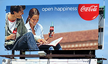 A premiere panel billboard featuring Coca-Cola 'open happiness'