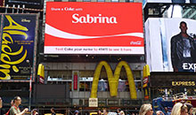 An HD digital video billboard encourages pedestrians in Times Square to 'Share a Coke'