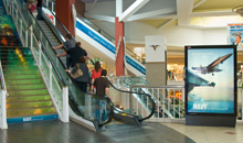 A branded staircase and directory display greet mall shoppers.